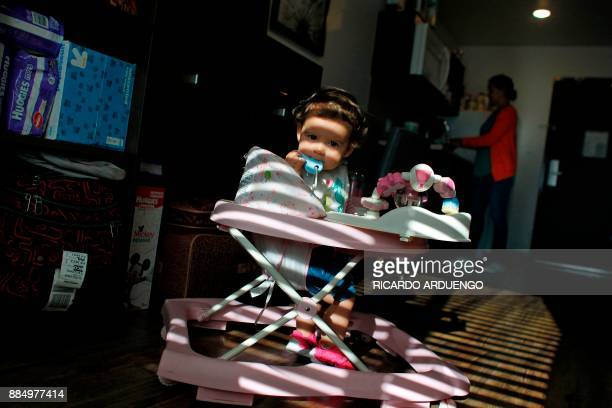 Genesis Rivera 10mo sits on her walker while her mother Deborah Oquendo prepare breakfast at the hotel were they are staying in Orlando Florida on...