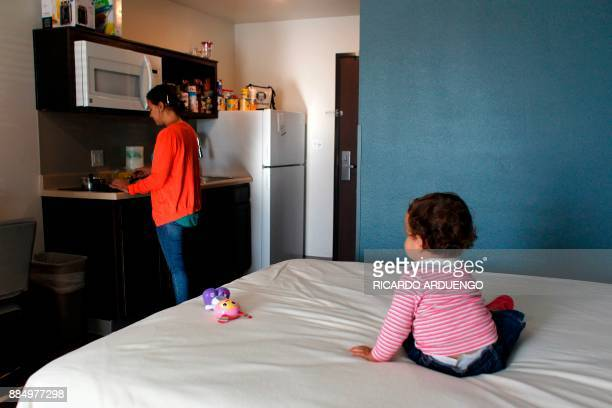 Genesis Rivera 10mo watches her mother Deborah Oquendo prepare breakfast at the hotel were they are staying in Orlando Florida on December 1 2017 On...