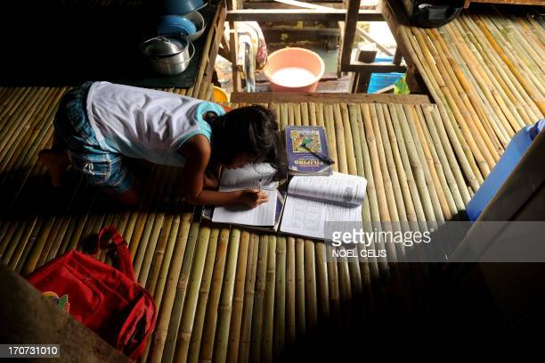 Genesis Tuazon 8 years old grade three student at the Pangulo Elementary School works on her school assignment inside her house at the Artex Compound...