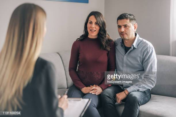 genetic counseling consultant advising couple during pregnancy - alternative therapy stock pictures, royalty-free photos & images
