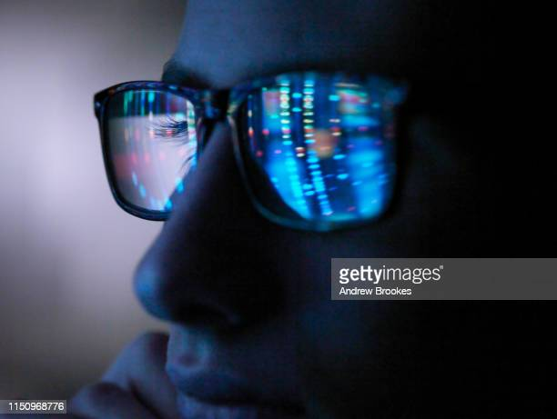 genetic research, computer screen reflection in spectacles of dna profile, close up of face - onderzoek stockfoto's en -beelden