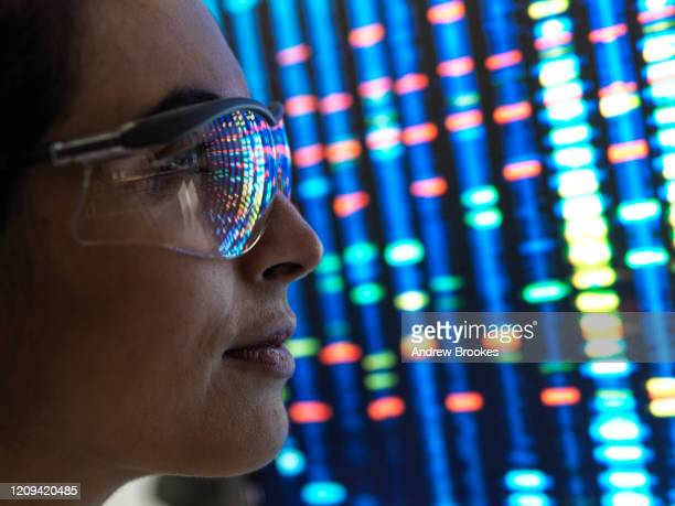genetic research, female scientist viewing a dna profile of a human sample on a screen in the lab. - genetic research stock pictures, royalty-free photos & images