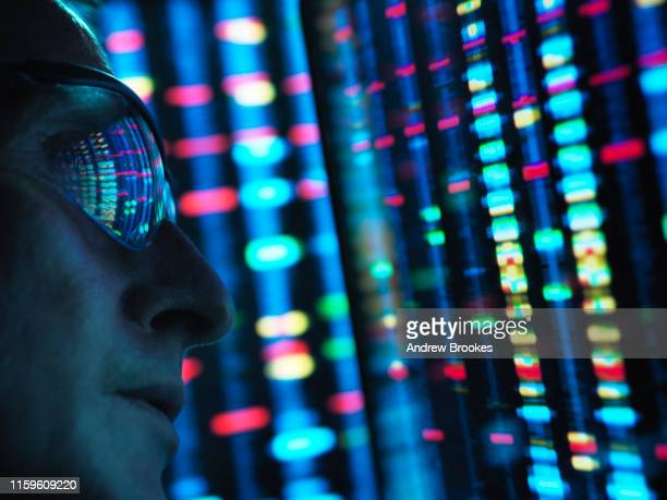 genetic research, scientist viewing dna information on screens, close up - multi coloured stock pictures, royalty-free photos & images