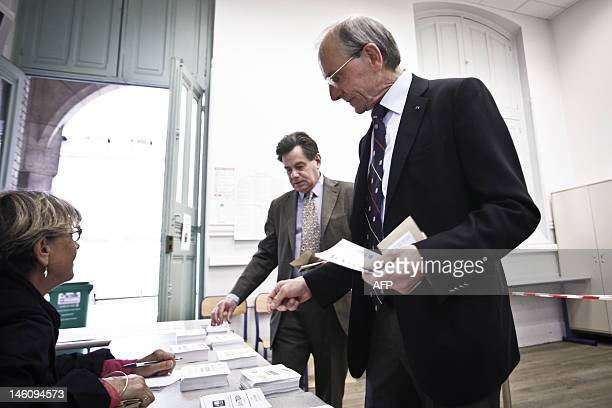 Geneticist and Socialist Party candidate in the 2nd constituency of Paris, Axel Kahn, picks up ballots before casting his vote for the first round of...