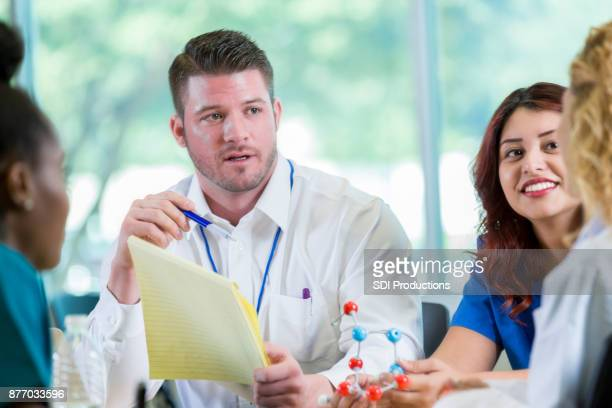 geneticist meets with group of doctors - geneticist stock pictures, royalty-free photos & images