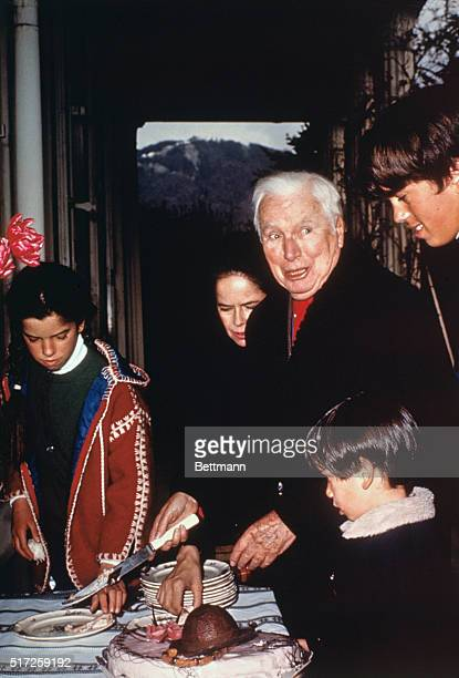 Geneva Switzerland Cutting a tiny birthday cake shaped like his onetime famous derby hat veteran comedian Charlie Chaplin celebrates his 80th...