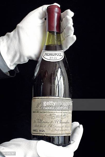 Picture taken 11 May 2007 shows a Christie's employee displaying a rare bottle of 1945 vintage Romanee-Conti wine of France during a preview in...