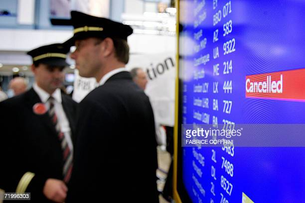 Swiss International Air Lines pilots stand next a screen showing a cancellation of a flight during a strike at Geneva Airport 26 September 2006 Swiss...