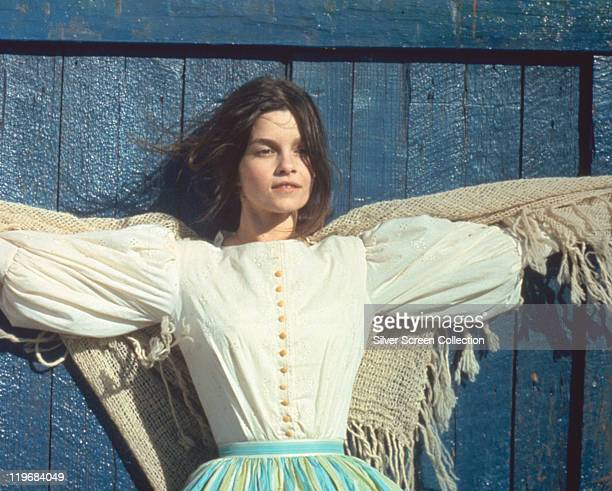 Genevieve Bujold Canadian actress wearing a white blouse with her arms outstretched either side of her with a shawl standing against a blue wooden...