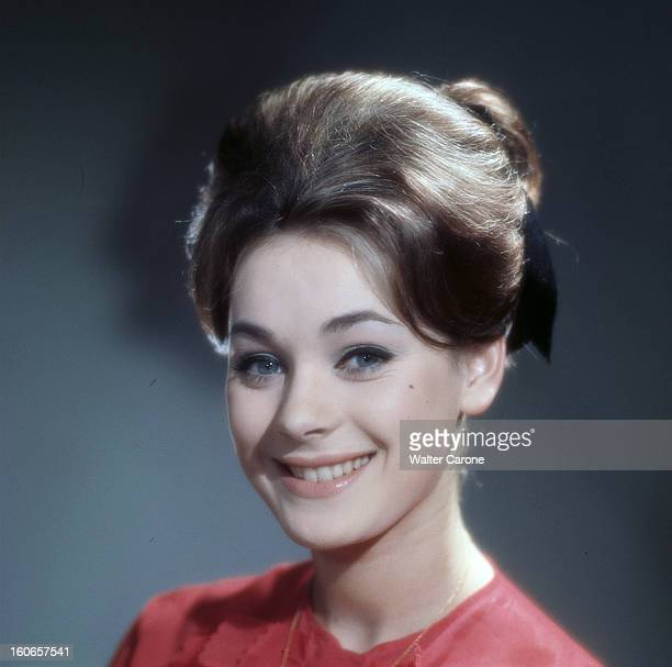Genevieve Grad Poses In Studio Portrait de Geneviève GRAD portant un chemisier rouge cheveux noués en chignon à l'arrière