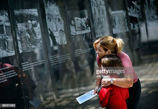 Genevieve Pared hugs her son Jason Pared as they look at photographs on display as they visit the Holocaust Memorial during Yom HaShoahHolocaust...