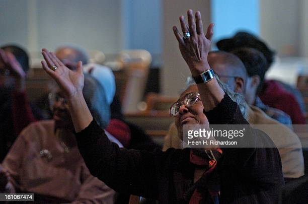 Genevieve Smith lifts up her hands to join in the singing during the service of her friend A memorial service celebrating and honoring the life of...