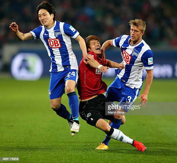 Genki Haraguchi and Per Ciljan Skjelbred of Hertha BSC challenge Hiroshi Kiyotake of Hannover 96 during the Bundesliga match between Hannover 96 and...