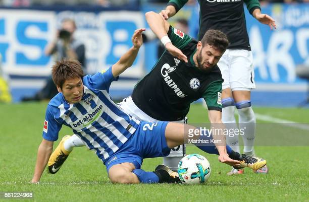 Genki Haraguchi of Berlin battles for the ball with Daniel Caligiuri of Schalke during the Bundesliga match between Hertha BSC and FC Schalke 04 at...