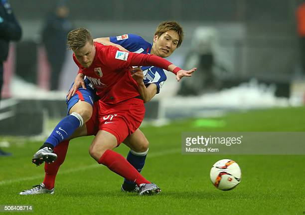 Genki Haraguchi of Berlin battles for the ball with Philipp Max of Augsburg during the Bundesliga match between Hertha BSC and FC Augsburg at...