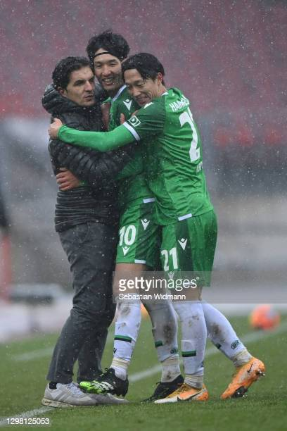 Genki Haraguchi of Hannover 96 celebrates with head coach Kenan Kocak and team mate Sei Muroya after scoring his team's third goal during the Second...