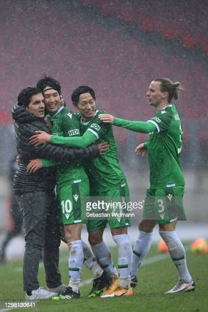 Genki Haraguchi of Hannover 96 celebrates with head coach Kenan Kocak and team mates Sei Muroya and Niklas Hult after scoring his team's third goal...