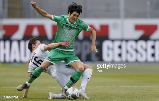 Genki Haraguchi of Hannover in action against Kevin Behrens of Sandhausen during the Second Bundesliga match between SV Sandhausen and Hannover 96 at...