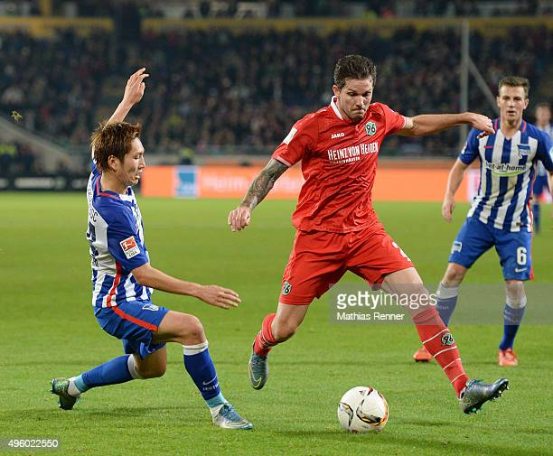 Genki Haraguchi of Hertha BSC and Leon Andreasen of Hannover 96 during the Bundesliga match between Hannover 96 and Hertha BSC at HDIArena on...