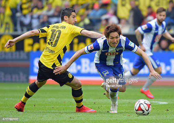 Genki Haraguchi of Hertha BSC handles the ball against Henrikh Mkhitayan of Borussia Dortmund during the game between Borussia Dortmund and Hertha...