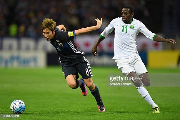 Genki Haraguchi of Japan and Abdulmalek Al Khaibri of Saudi Arabia compete for the ball during the 2018 FIFA World Cup Qualifier match between Japan...