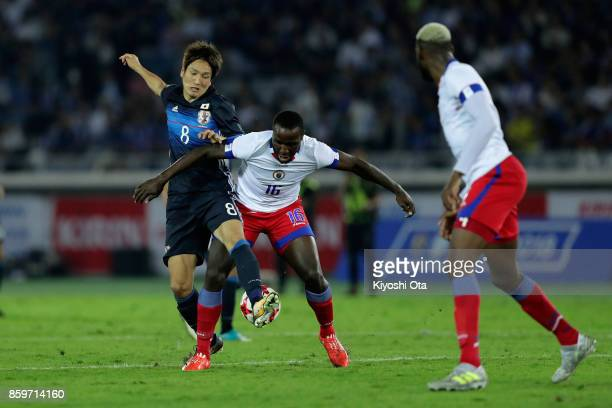 Genki Haraguchi of Japan and Andrew Anderson JeanBaptiste of Haiti compete for the ball during the international friendly match between Japan and...