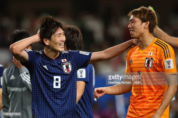 Genki Haraguchi of Japan celebrates with Masaaki Higashiguchi of Japan at the end of the AFC Asian Cup semi final match between Iran and Japan at...
