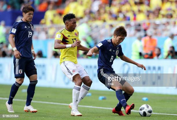 Genki Haraguchi of Japan holds off Johan Mojica of Colombia as Hiroki Sakai of Japan looks on during the 2018 FIFA World Cup Russia group H match...