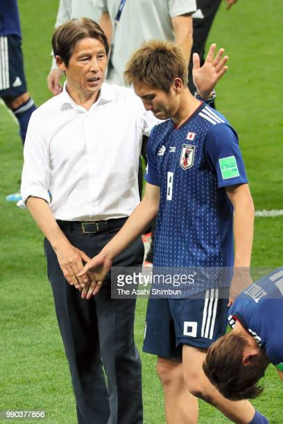Genki Haraguchi of Japan is consoled by head coach Akira Nishino after their 23 defeat in the 2018 FIFA World Cup Russia Round of 16 match between...