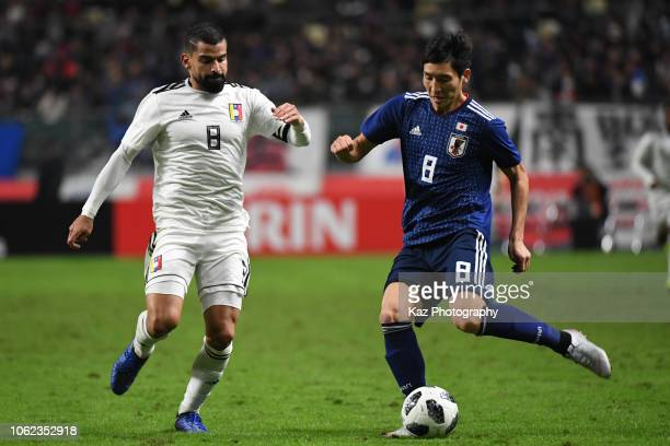 Genki Haraguchi of Japan passes the ball under the pressure from Tomas Rincon of Venezuela during the international friendly match between Japan and...