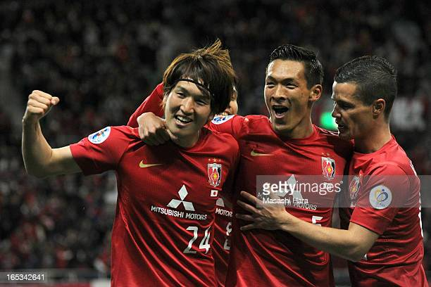 Genki Haraguchi of Urawa Red Diamonds celebrates the first goal with Tomoaki Makino and Marcio Richardes during the AFC Champions League Group F...