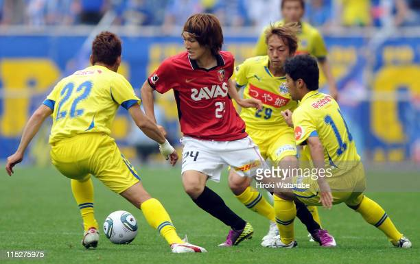 Genki Haraguchi of Urawa Red Diamonds competes for the ball with Takuya Sonoda, Takuya Miyamoto and Tomoyasu Hirose of Montedio Yamagata during the...