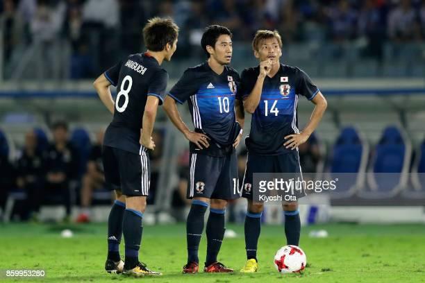 Genki Haraguchi Shinji Kagawa and Takashi Inui of Japan talk before a free kick during the international friendly match between Japan and Haiti at...