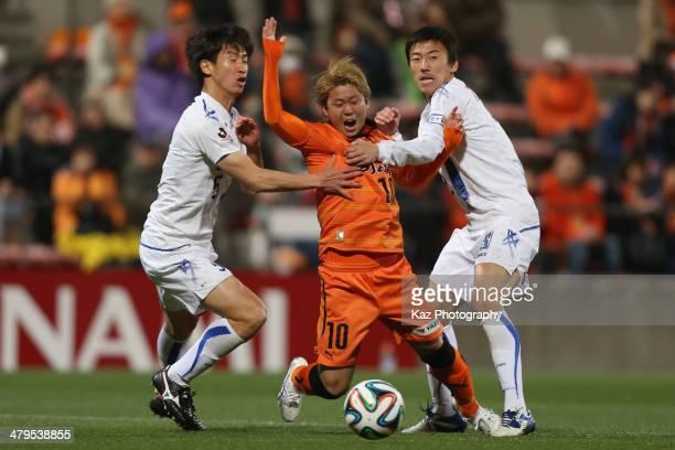 Genki Omae of Shimizu S-Pulse is tackled by Naoki Ishikawa and Jiro Kamata of Vegalta Sendai during the J.League Yamazaki Nabisco Cup match between...