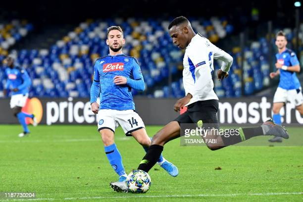 RC Genk's Colombian defender Jhon Lucumi shoots on goal despite Napoli's Belgian forward Dries Mertens during the UEFA Champions League Group E...