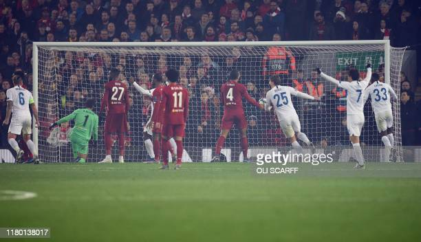 RC Genk's Tanzanian forward Mbwana Ally Samatta scores past Liverpool's Brazilian goalkeeper Alisson Becker to equalise during the UEFA Champions...