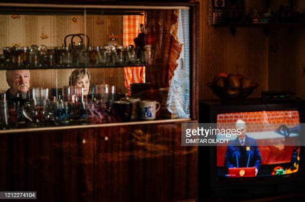 Gennady Matveiev with his wife Galina watch the television screen showing Russian President Vladimir Putin's address to the nation marking the 75th...