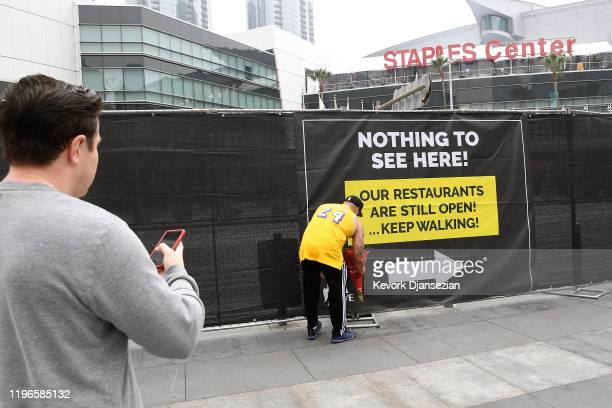 Gennesys Cabral reacts to the news that former NBA player Kobe Bryant died in a helicopter crash as he leaves flowers outside the Staples Center...