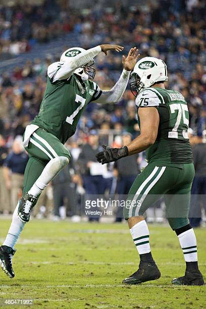 Geno Smith jumps into the arms of Oday Aboushi of the New York Jets after a touchdown in the fourth quarter of a game against the Tennessee Titans at...
