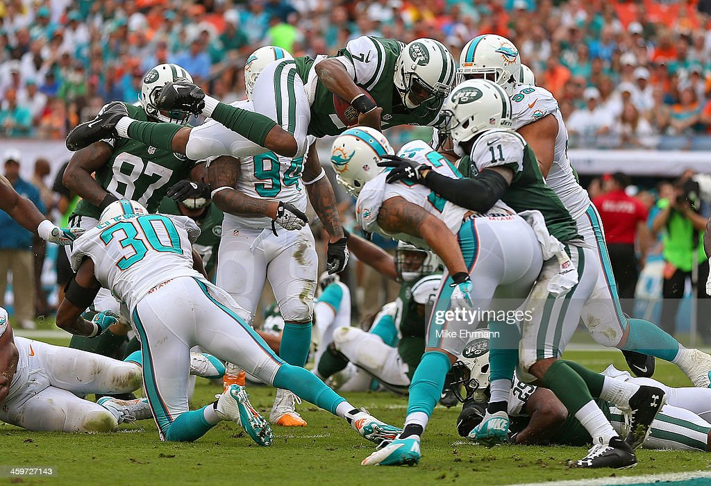 Geno Smith #7 of the New York Jets dives for a first down during a game against the Miami Dolphins at Sun Life Stadium on December 29, 2013 in Miami Gardens, Florida.