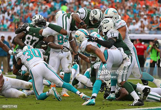 Geno Smith of the New York Jets dives for a first down during a game against the Miami Dolphins at Sun Life Stadium on December 29 2013 in Miami...