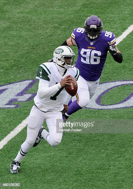 Geno Smith of the New York Jets scrambles under pressure from Brian Robison of the Minnesota Vikings during the first quarter of the game on December...