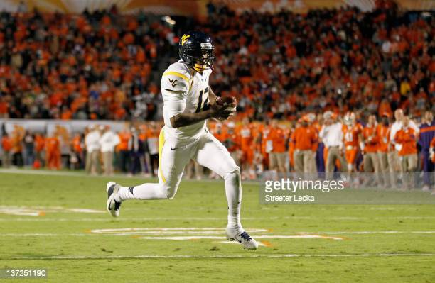 Geno Smith of the West Virginia Mountaineers scores a 7yard rushing touchdown in the second quarter against the Clemson Tigers during the Discover...