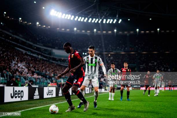 Genoa's Colombian defender Cristian Zapata challenges Juventus' Portuguese forward Cristiano Ronaldo during the Italian Serie A football match...