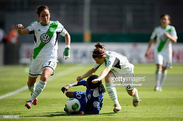 Genoveva Anonma of Potsdam is challenged by Nadine Kessler and Maren Tetzlaff of Wolfsburg during the Women's DFB Cup Final between VfL Wolfsburg and...