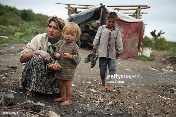 Genoveva Lingurar who is pregnant feeds her son Alexandru a potatoe baked in a campfire as another of her children Andrei approaches outside the...