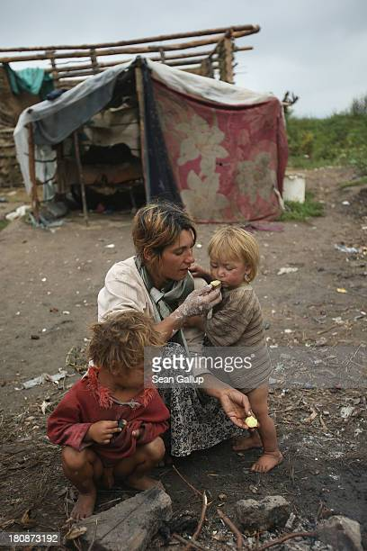 Genoveva Lingurar who is pregnant feeds her son Alexandru a potatoe baked in a campfire while another of children Aramndo squats next to her outside...