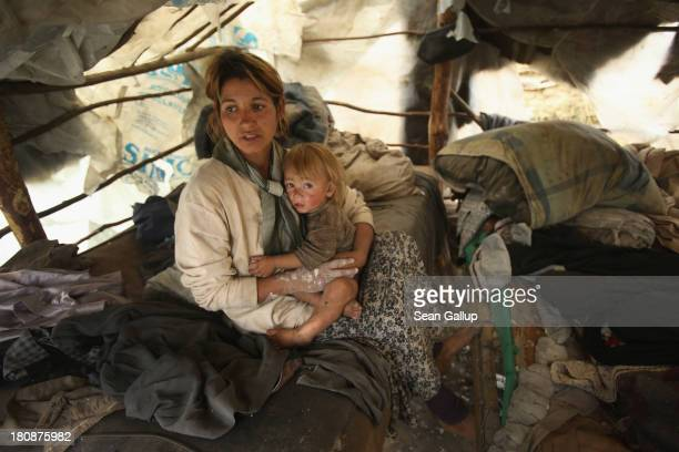 Genoveva Lingurar who is pregnant holds her son Alexandru in the makeshift and temporary home she shares with her husband and seven children in the...