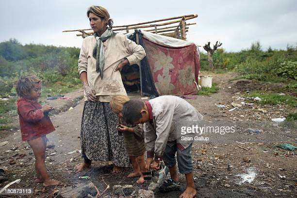Genoveva Lingurar who is pregnant stands at a fire with her children Alexandru Armando and Andrei outside the makeshift and temporary home she shares...