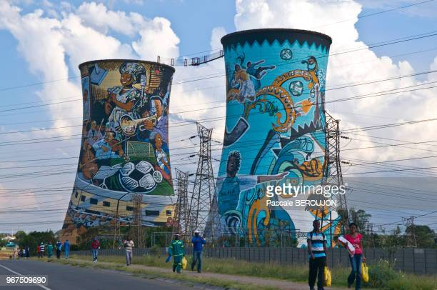 Gens marchant devant les 2 tours de refroidissement plus en activite, fresques murales representant les moments et les gens importants de Soweto,...